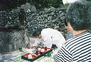 井戸で儀式を執り行う老女